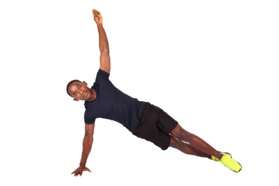 Athletic male doing side plank with one arm raised