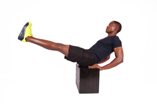 Athletic male doing v ups ab exercise on step up box