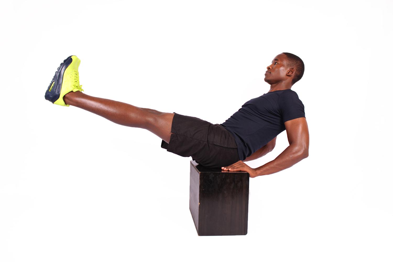 Athletic male doing v ups ab exercise on step up box