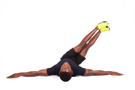 Athletic male doing windshield wiper obliques exercise