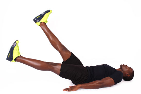 Athletic man doing flutter kicks ab exercise