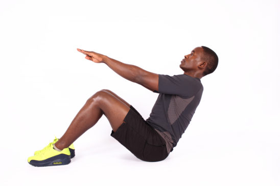 Athletic man doing sit ups exercise with legs bent