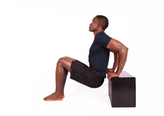 Athletic man doing triceps bench dips exercise