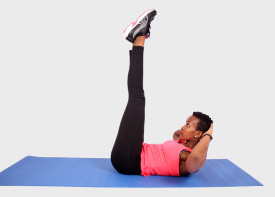 Athletic woman doing crunches with legs raised