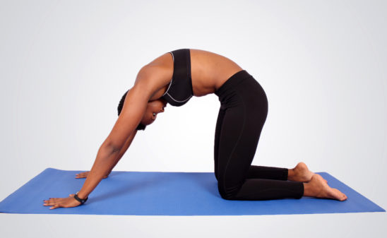 Athletic woman doing doing yoga pose to stretch back