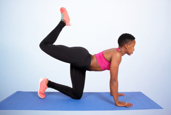 Athletic woman doing donkey kick exercise