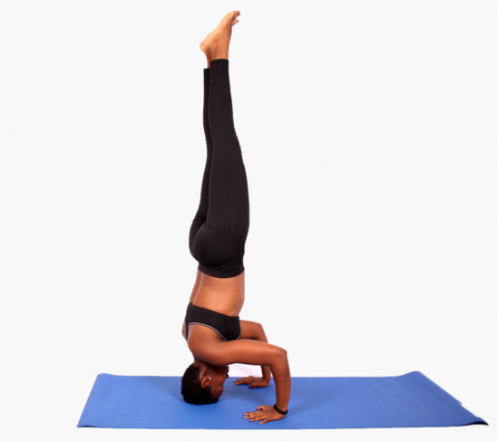 Athletic woman doing headstand on blue yoga mat
