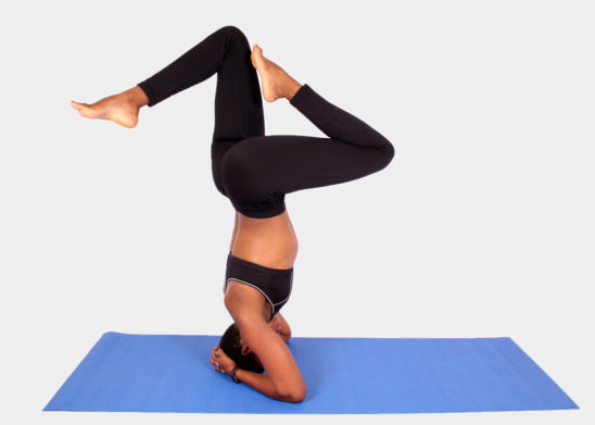 Athletic woman doing headstand yoga pose
