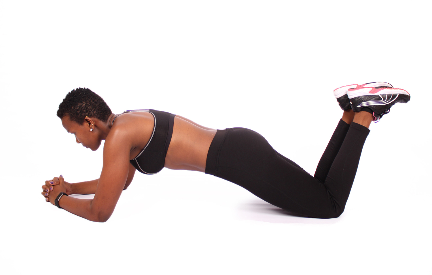 Athletic woman doing knee plank on isolated background
