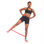 Athletic woman doing side kick resistance band exercise