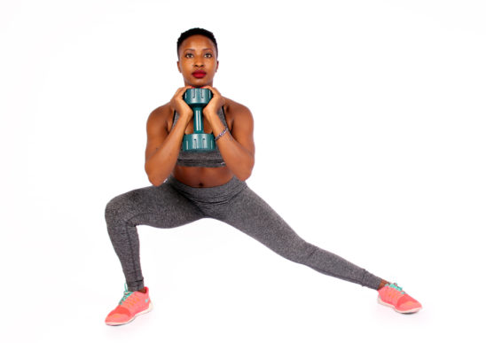 Athletic woman doing side lunge with dumbbells