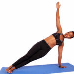 Athletic woman doing side plank yoga pose