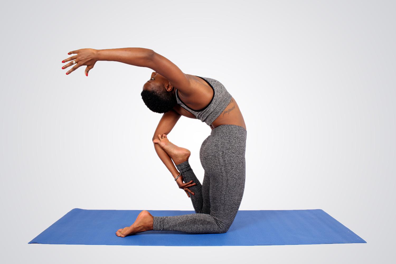 Athletic woman doing yoga kneeling on yoga mat