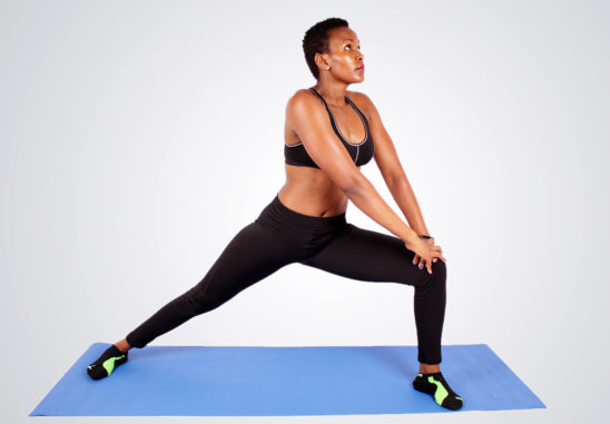 Athletic woman stretching legs on yoga mat