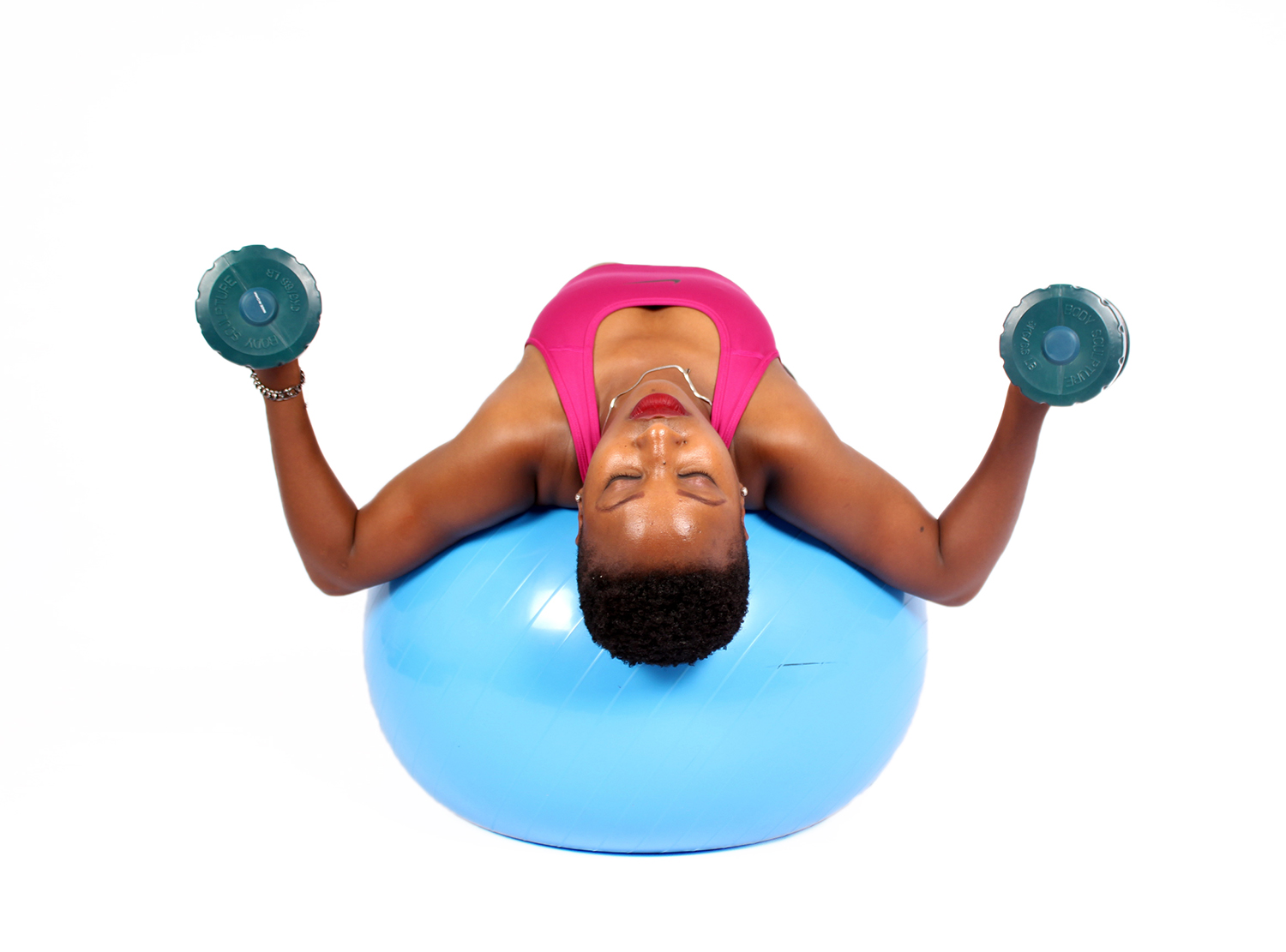 Beautiful Woman Lifting Dumbbells while Lying on Swiss Ball