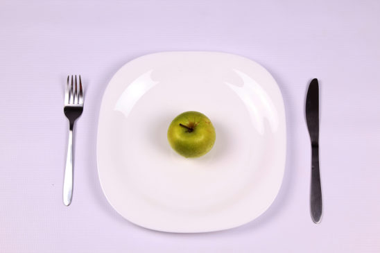 Dieting concept. Plate, Apple, Folk, and Knife