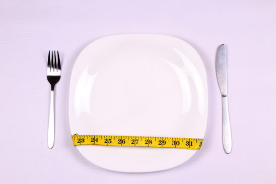 Dieting concept with tape measure wrapped around plate