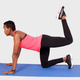 Fit african woman doing donkey kick exercise