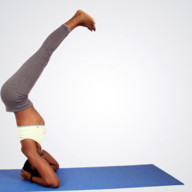 Fit african woman doing headstand yoga pose