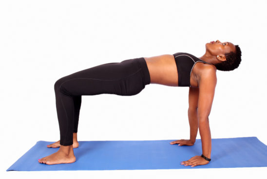 Fit african woman doing table maker yoga pose