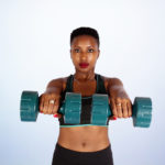 Fit African Woman Lifting a Pair of Dumbbells