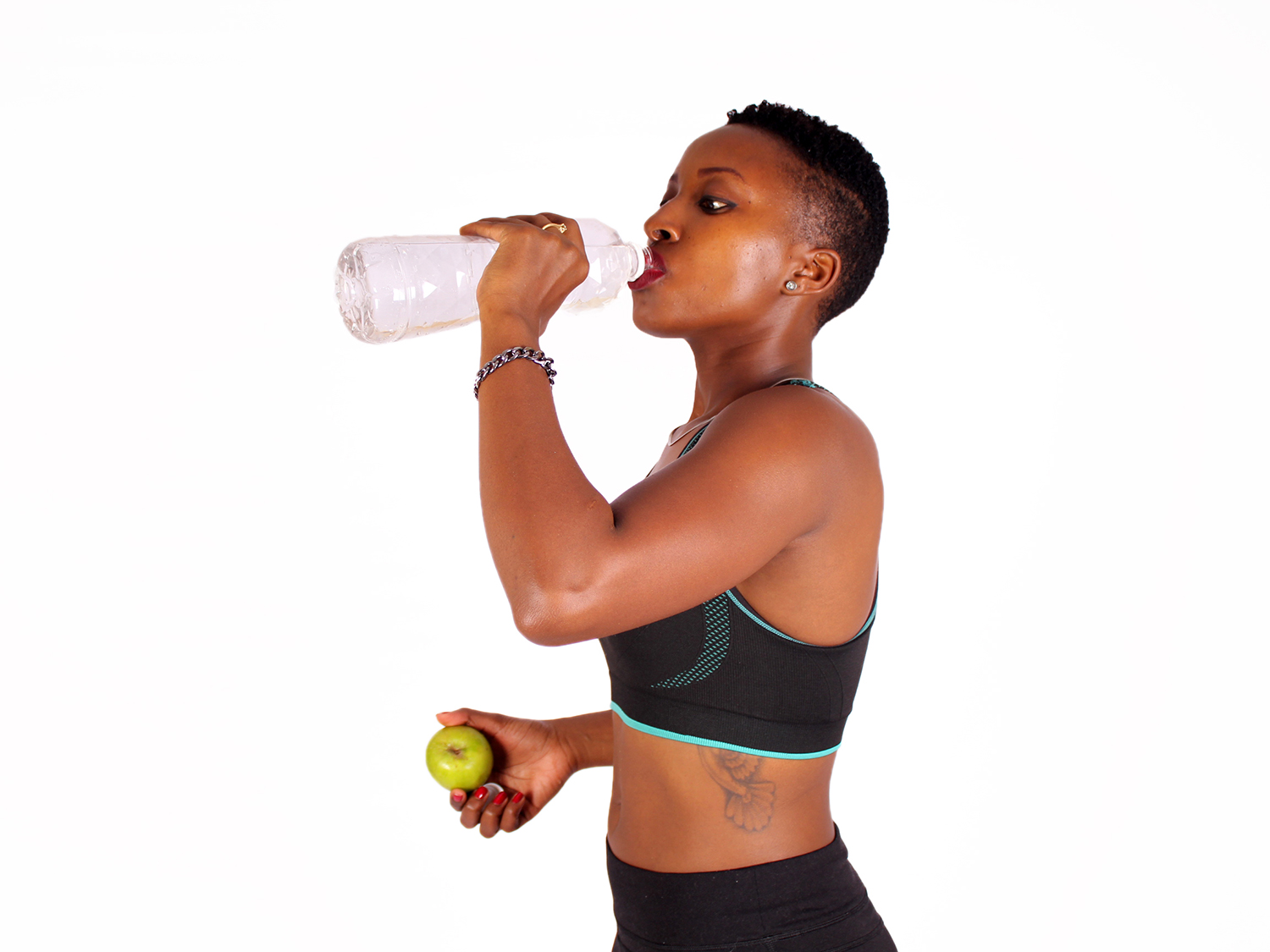 Fit athletic woman drinking water holding apple