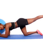 Fit athletic woman exercising next to swiss ball