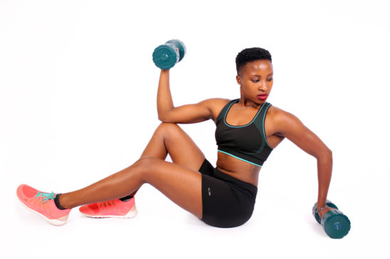 Fit athletic woman exercising with dumbbells