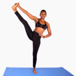 Fit athletic woman stretching leg while standing