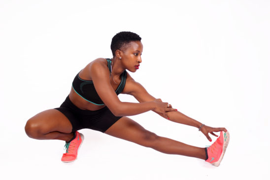 Fit athletic woman stretching legs touch toes