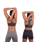 Fit athletic women stretching shoulders and triceps