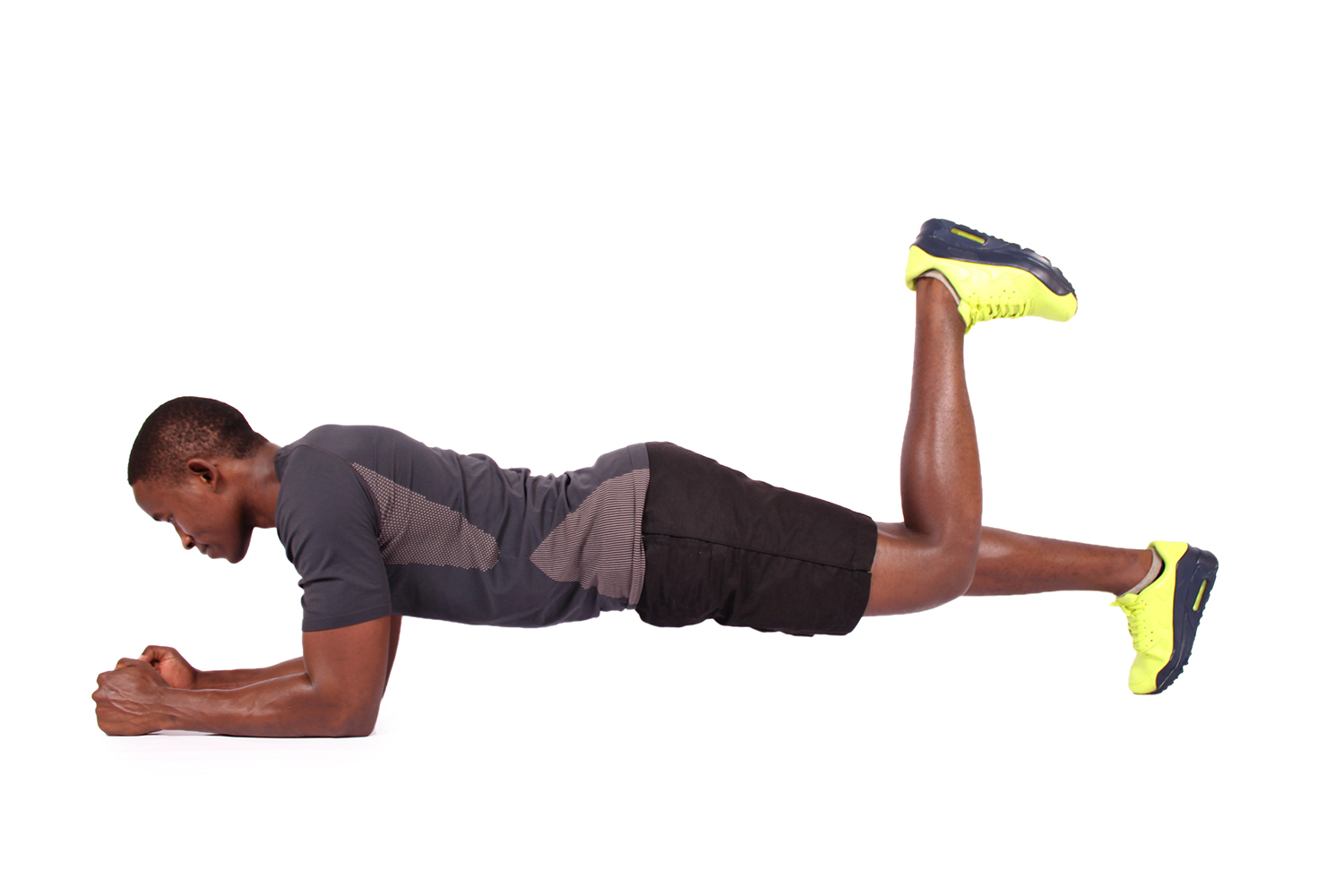 Fit man doing front plank with one leg raised