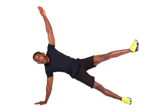 Fit man doing side plank with arm and leg raised