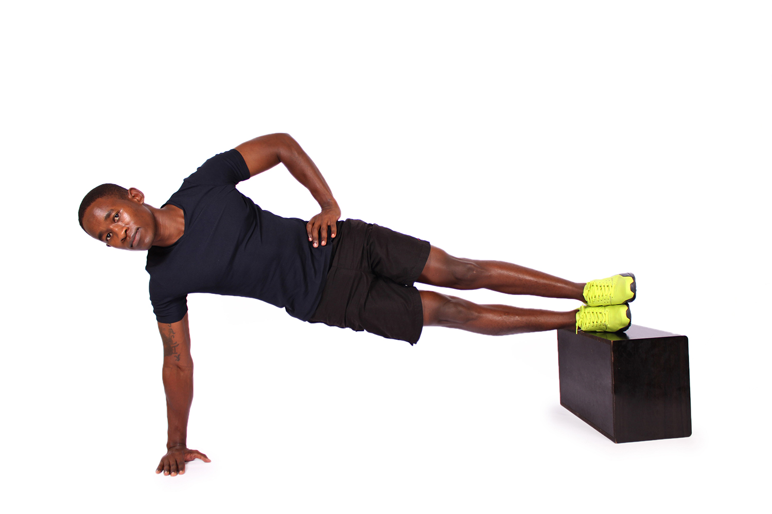Fit man doing side plank with feet elevated