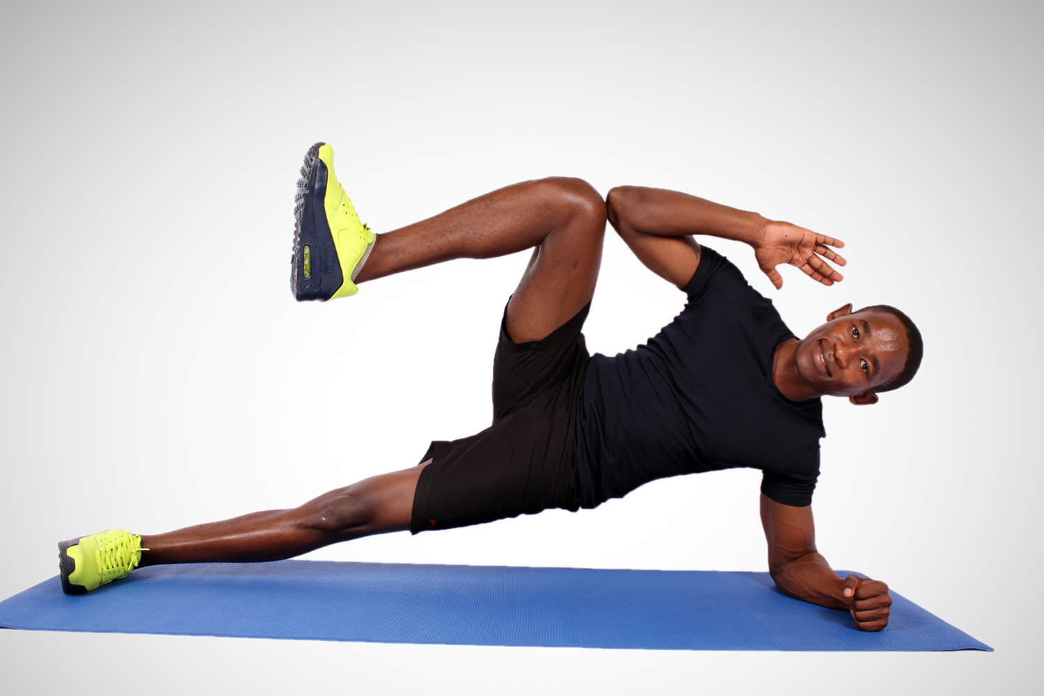 Fit man doing side plank with knee crunch on yoga mat