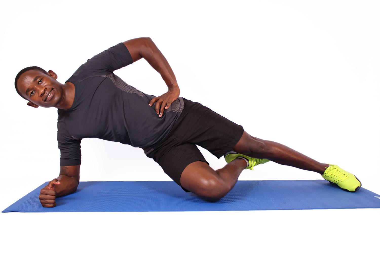 Fit man doing single leg side plank