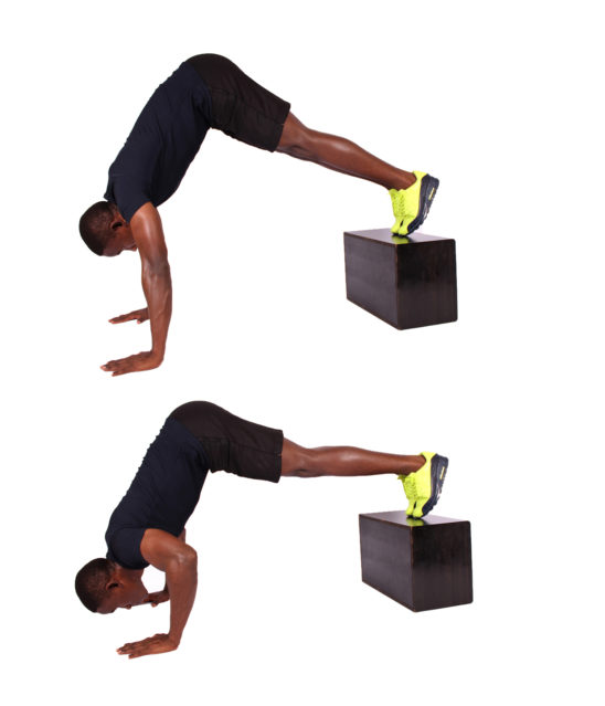 Fit man shows how to do pike push ups with feet elevated