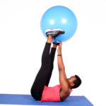 Fit woman doing ab exercise with swiss ball