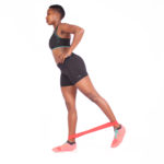Fit woman doing back kicks with resistance bands