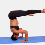 Fit woman doing headstand yoga exercise