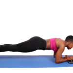 Fit woman doing plank using laptop