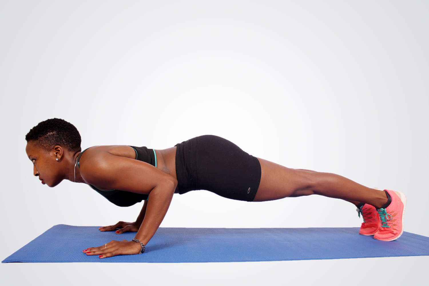 Fit woman doing push ups on blue yoga mat