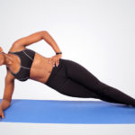 Fit woman doing side plank on yoga mat