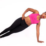 Fit woman doing side plank with hand on hips