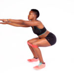 Fit woman doing squats with resistance bands