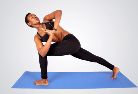 Fit woman doing yoga pose standing on yoga mat