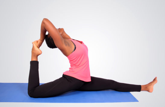 Fit woman doing yoga stretch on yoga mat