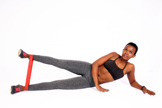 Fit woman exercising with resistance bands side leg raises