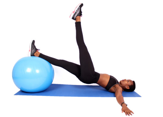 Fit woman exercising with swiss ball