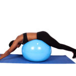 Fit woman lying on swiss ball bacl exercise
